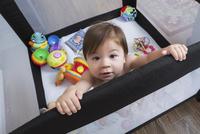 Mixed race baby girl standing in playpen