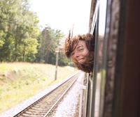 Hispanic woman with head out train window