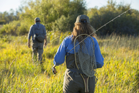 Caucasian couple with fishing gear in field