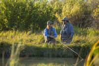 Caucasian couple fishing in river