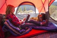 Caucasian woman using digital tablet in camping tent