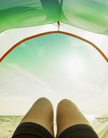 Legs in camping tent door on beach