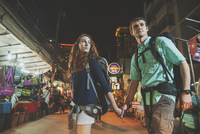 Caucasian tourists holding hands in market at night