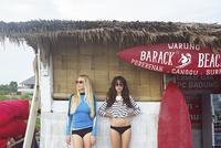 Caucasian women standing at surf hut on beach 11018062226| 写真素材・ストックフォト・画像・イラスト素材|アマナイメージズ