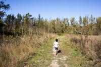 Mixed race boy walking on dirt path