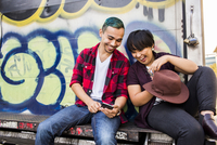Friends using cell phone on graffiti truck