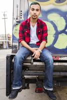 Hispanic man sitting on graffiti truck
