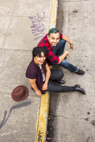 High angle view of couple sitting on curb