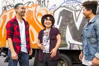 Friends laughing at graffiti wall