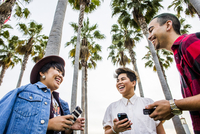 Low angle view of friends using cell phones outdoors