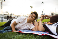 Asian friends laying in grass