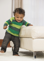 Mixed race baby boy walking on carpet