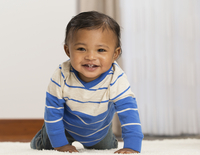 Mixed race baby boy crawling on carpet