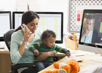 Mother with baby son working at home office