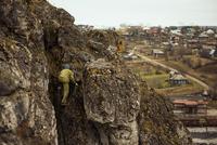 Hiker climbing rocky mountainside