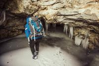 Caucasian woman exploring stalactites in cave