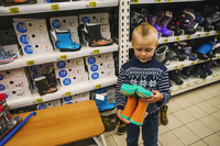 Caucasian boy admiring boots in store