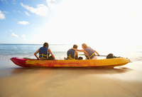 Friends sitting in canoe on beach