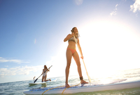 Women paddle boarding in ocean
