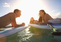 Friends talking on paddle boards in ocean