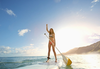 Woman standing on paddle board in ocean
