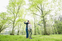 Caucasian couple photographing in field