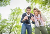 Caucasian couple photographing outdoors