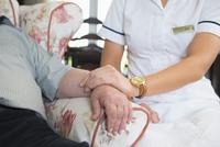 Caucasian nurse measuring pulse of patient in home
