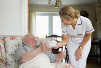 Caucasian nurse serving patient tea in home