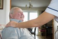 Caucasian nurse comforting patient in home