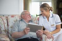 Caucasian nurse and patient using digital tablet