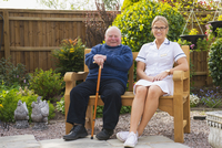 Caucasian nurse and patient sitting in garden