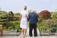 Caucasian nurse and patient walking in garden 11018062683| 写真素材・ストックフォト・画像・イラスト素材|アマナイメージズ