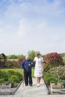 Caucasian nurse and patient walking in garden