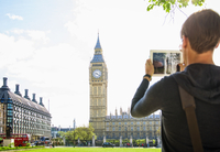 Caucasian man photographing clock tower, London, Middlesex, United Kingdom