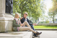 Caucasian couple holding map at statue