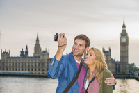 Caucasian couple taking selfie at clock tower, London, Middlesex, United Kingdom
