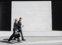 Caucasian business people walking on sidewalk