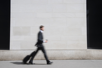 Caucasian businessman walking on sidewalk 11018062757| 写真素材・ストックフォト・画像・イラスト素材|アマナイメージズ
