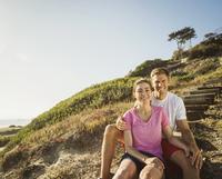 Caucasian couple sitting on hillside