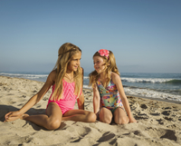 Caucasian sisters smiling on beach