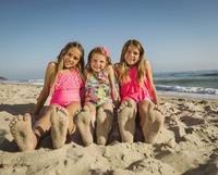 Caucasian sisters with sandy feet on beach