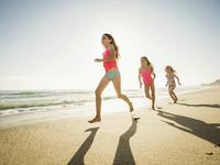 Caucasian sisters running on beach