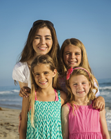 Caucasian mother and daughters smiling on beach