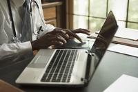Black doctor using digital tablet in office 11018062844| 写真素材・ストックフォト・画像・イラスト素材|アマナイメージズ