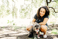 Black woman petting dog outdoors