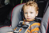Caucasian boy sitting in car seat