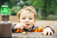 Caucasian boy eating snack at picnic table