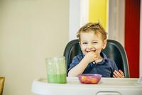Caucasian boy eating in high chair