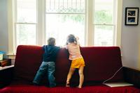 Caucasian children standing on sofa